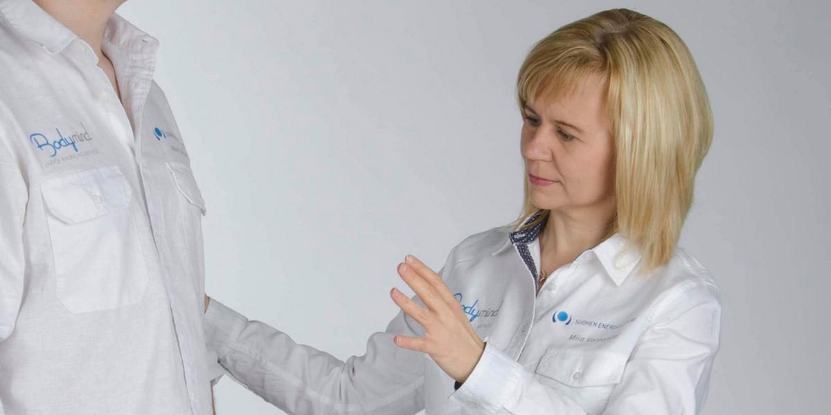 nainen antaa energiahoitoa asiakkaalle